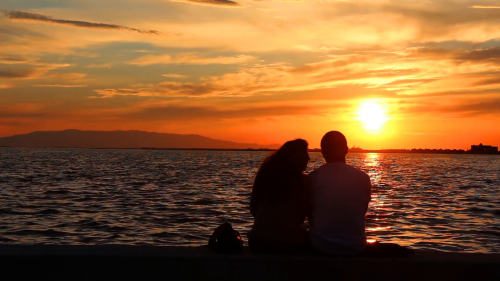 loving-couple-on-the-beach-sitting-sunset_4uuls4t3x__f0000