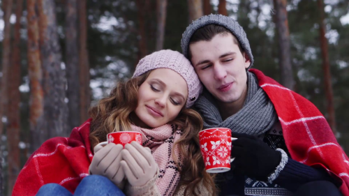 young-couple-sitting-by-bonfire-and-drinking-coffee-in-winter-forest_swx3rzoowl_thumbnail-full01