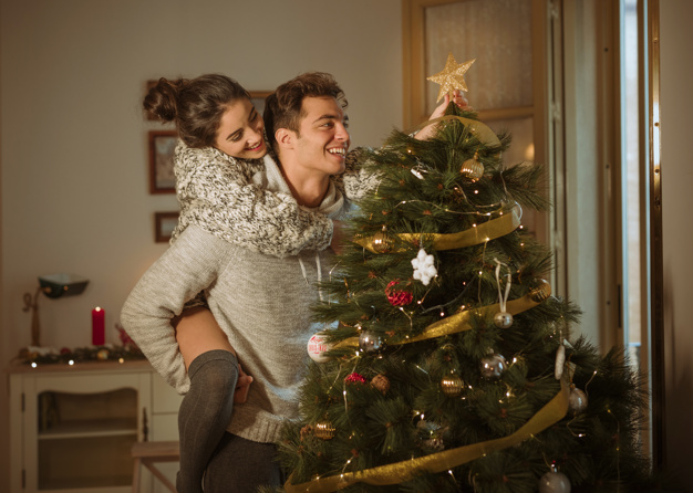happy-couple-decorating-christmas-tree-with-star_23-2147978591